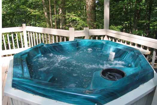 Hot tub on the deck surrounded by the woods at Heavenly Hideaway, a 2-bedroom cabin rental located in Gatlinburg