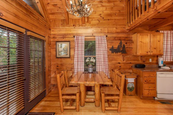 Log dining table with seating for four and an antler chandelier at Cabin in the Woods, a 1-bedroom cabin rental located in Pigeon Forge