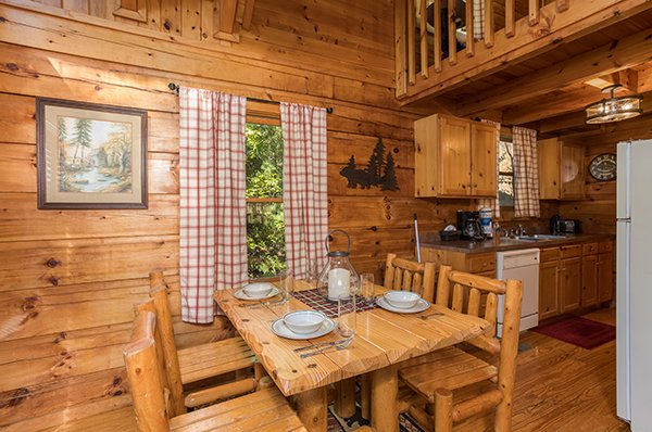 Dining table with seating for four and a kitchen with white appliances at Cabin in the Woods, a 1-bedroom cabin rental located in Pigeon Forge