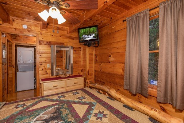 Dresser with a mirror and wall-mounted television at Cabin in the Woods, a 1-bedroom cabin rental located in Pigeon Forge