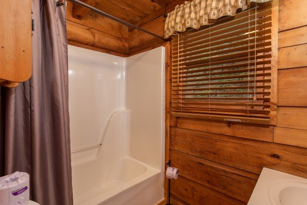 Bathroom with a tub and shower at Cabin in the Woods, a 1-bedroom cabin rental located in Pigeon Forge