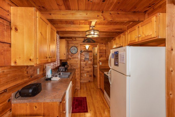 Galley kitchen with white appliances at Cabin in the Woods, a 1-bedroom cabin rental located in Pigeon Forge