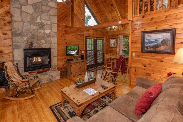 Living room with stone fireplace and television at Cabin in the Woods, a 1-bedroom cabin rental located in Pigeon Forge