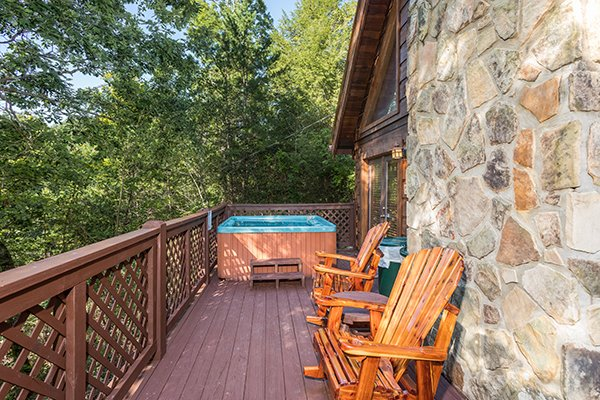 Adirondack rocking chairs and a hot tub on the deck at Cabin in the Woods, a 1-bedroom cabin rental located in Pigeon Forge