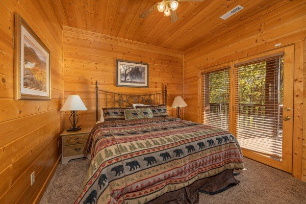 Bedroom with queen bed, two night stands, and deck access at Grizzly's Den, a 5 bedroom cabin rental located in Gatlinburg
