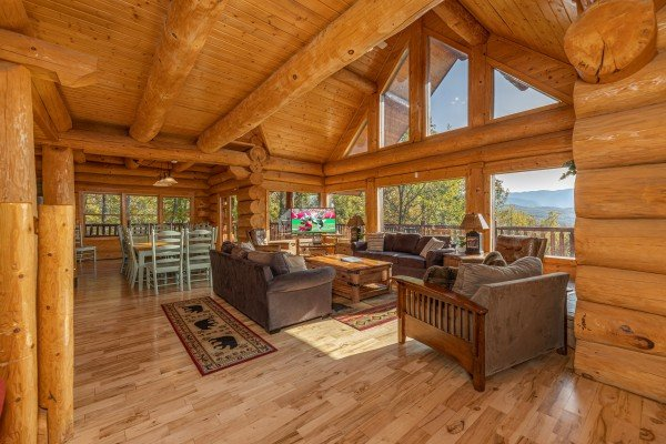 Vaulted living room with large windows at Grizzly's Den, a 5 bedroom cabin rental located in Gatlinburg