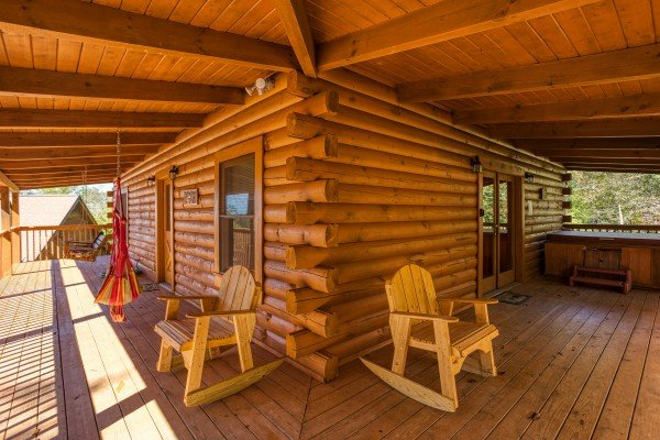 Covered porch with rocking chairs, hammock, and hot tub at Skyline Retreat, a 2 bedroom cabin rental located in Sevierville