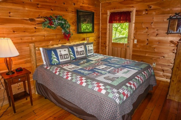 King sized bed in bedroom at Moonlight in the Boondocks, a 2 bedroom cabin rental located in Gatlinburg