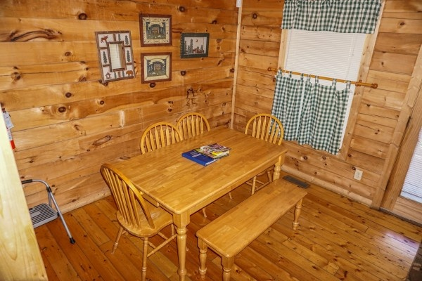 Dining table with four chairs and a bench at Moonlight in the Boondocks, a 2 bedroom cabin rental located in Gatlinburg