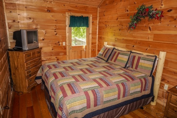 King sized bedroom with deck access and en suite at Moonlight in the Boondocks, a 2 bedroom cabin rental located in Gatlinburg