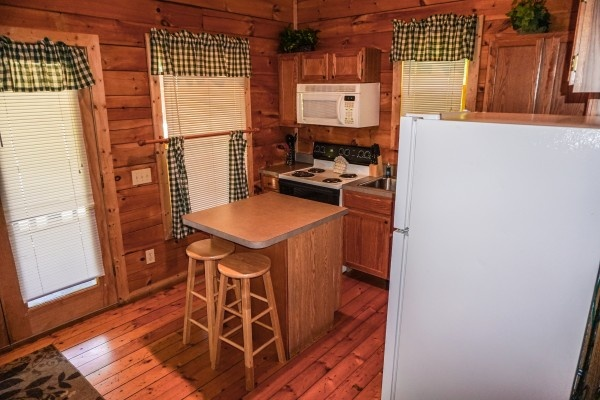 Kitchen with white appliances at Moonlight in the Boondocks, a 2 bedroom cabin rental located in Gatlinburg