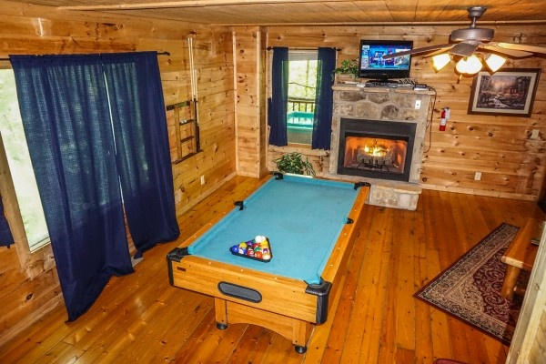 Living room with stone fireplace at Moonlight in the Boondocks, a 2 bedroom cabin rental located in Gatlinburg