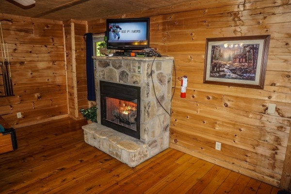 Stone fireplace in the living room at Moonlight in the Boondocks, a 2 bedroom cabin rental located in Gatlinburg