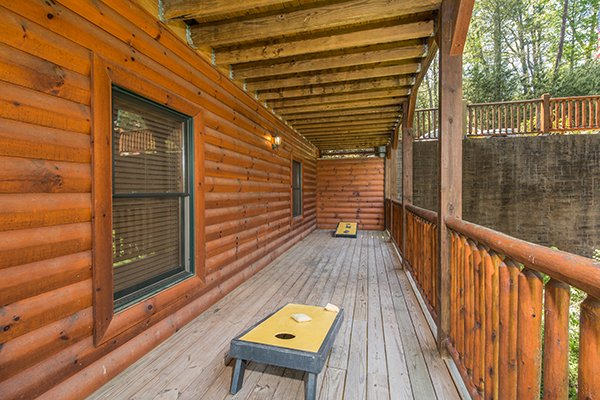 Corn hole on the covered deck at Honey Bear Lodge, a 3 bedroom cabin rental located in Gatlinburg