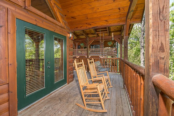 Rocking chairs on the covered deck at Honey Bear Lodge, a 3 bedroom cabin rental located in Gatlinburg
