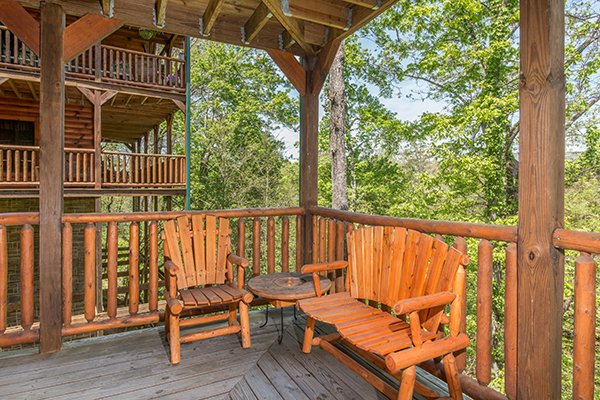 Bench and chair on the covered deck at Honey Bear Lodge, a 3 bedroom cabin rental located in Gatlinburg