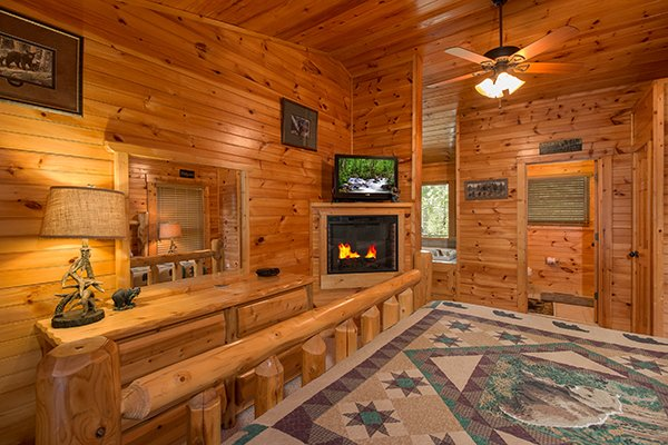 Bedroom with a fireplace and TV at Honey Bear Lodge, a 3 bedroom cabin rental located in Gatlinburg