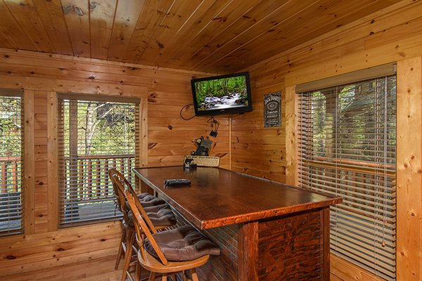 Bar top seating and a TV in the game room at Honey Bear Lodge, a 3 bedroom cabin rental located in Gatlinburg