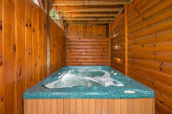 Hot tub on a covered porch with privacy fence at Honey Bear Lodge, a 3 bedroom cabin rental located in Gatlinburg