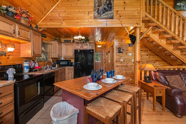 Kitchen with black appliances and island with seating for three at Honey Bear Lodge, a 3 bedroom cabin rental located in Gatlinburg