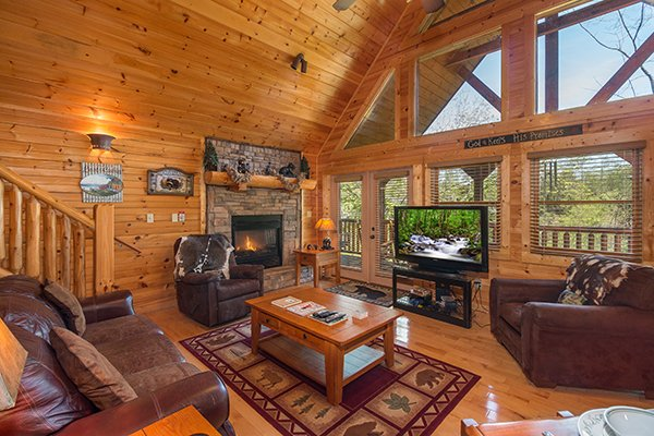 Living room with vaulted ceiling, large windows, fireplace, and TV at Honey Bear Lodge, a 3 bedroom cabin rental located in Gatlinburg