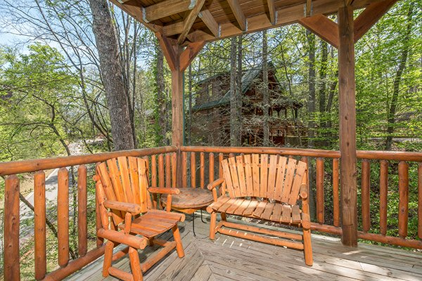 Chair and loveseat bench on the covered deck at Honey Bear Lodge, a 3 bedroom cabin rental located in Gatlinburg