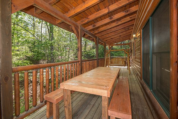 Picnic table on a covered deck at Honey Bear Lodge, a 3 bedroom cabin rental located in Gatlinburg