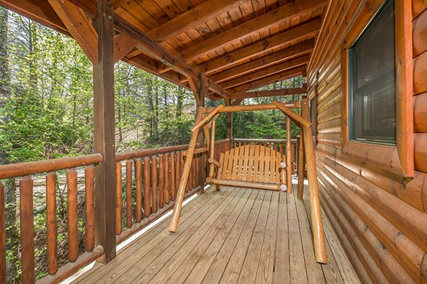 Swing on a covered porch at Honey Bear Lodge, a 3 bedroom cabin rental located in Gatlinburg