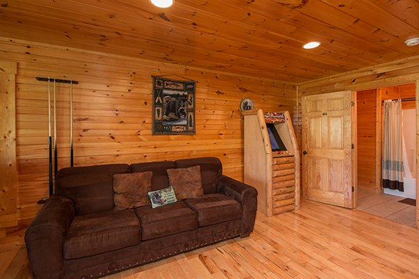 Sofa bed and arcade game in the game room at Honey Bear Lodge, a 3 bedroom cabin rental located in Gatlinburg