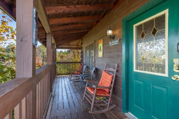 rocking chairs on the covered front porch at another day in bearadise a 2 bedroom cabin rental located in pigeon forge