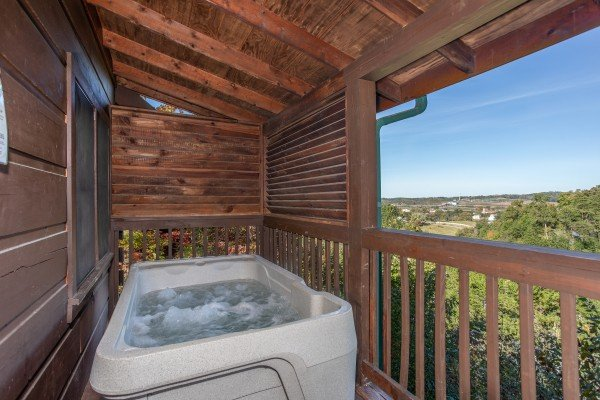 hot tub on a covered deck with privacy fence at another day in bearadise a 2 bedroom cabin rental located in pigeon forge
