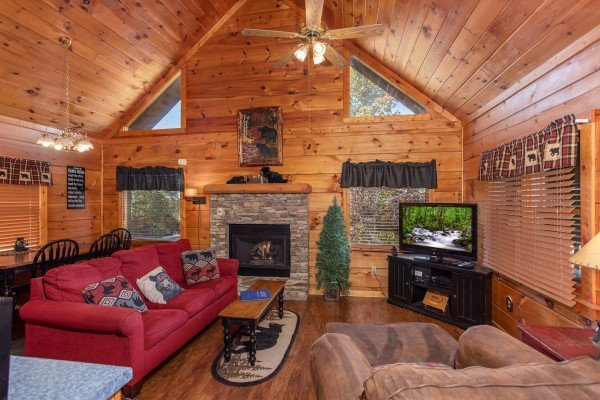 vaulted living room with stone fireplace at another day in bearadise a 2 bedroom cabin rental located in pigeon forge