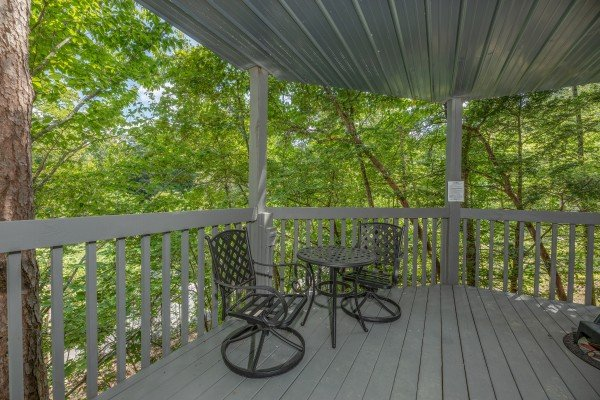 Bistro table on a covered deck at One Blessed Nest, a 3 bedroom cabin rental located in Pigeon Forge