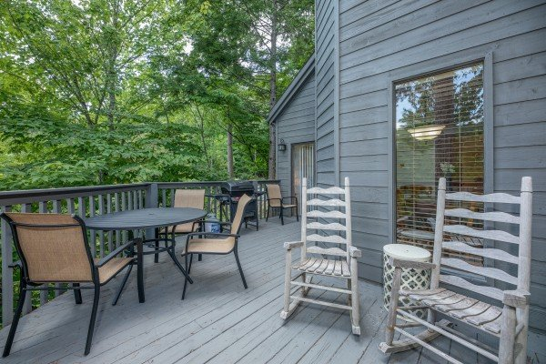 Rocking chairs and dining table on the deck at One Blessed Nest, a 3 bedroom cabin rental located in Pigeon Forge