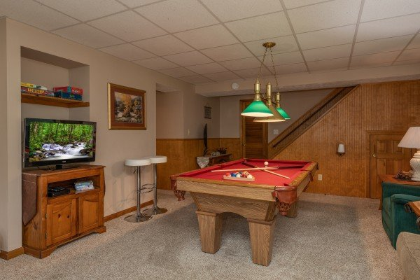 Pool table and TV in the lower living room at One Blessed Nest, a 3 bedroom cabin rental located in Pigeon Forge