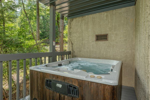 Hot tub on a covered deck at One Blessed Nest, a 3 bedroom cabin rental located in Pigeon Forge
