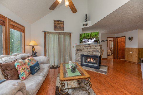 Fireplace, TV, and sofa in the living room at One Blessed Nest, a 3 bedroom cabin rental located in Pigeon Forge