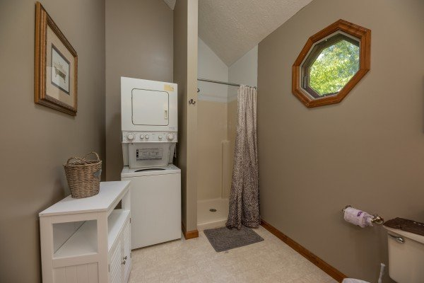 Stacked washer and dryer next to a shower stall in a bathroom at One Blessed Nest, a 3 bedroom cabin rental located in Pigeon Forge