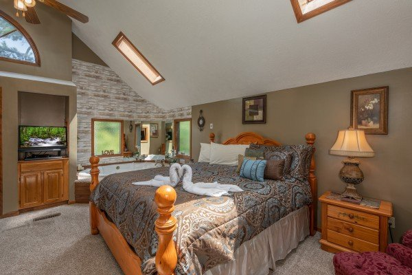 Master bedroom with skylights, king bed, and jacuzzi at One Blessed Nest, a 3 bedroom cabin rental located in Pigeon Forge
