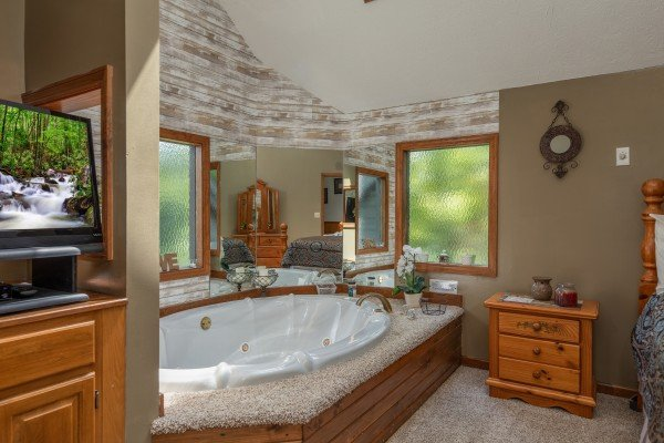 Jacuzzi tub and TV in the master bedroom at One Blessed Nest, a 3 bedroom cabin rental located in Pigeon Forge