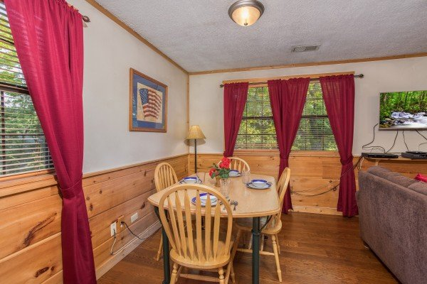 Dining table for four in the living room at Patriot Pointe, a 5 bedroom cabin rental located in Pigeon Forge