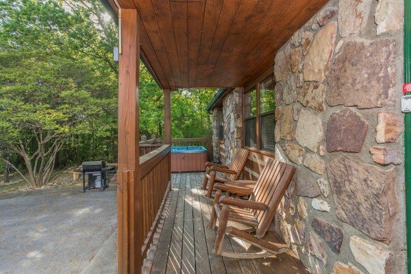 Porch with rocking chairs and a hot tub near a grill at Patriot Pointe, a 5 bedroom cabin rental located in Pigeon Forge