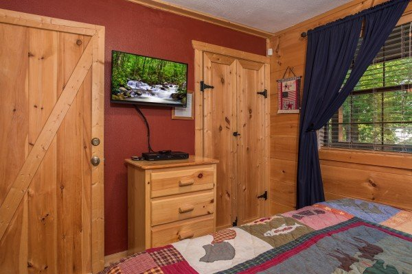 Dresser and TV in a bedroom at Patriot Pointe, a 5 bedroom cabin rental located in Pigeon Forge
