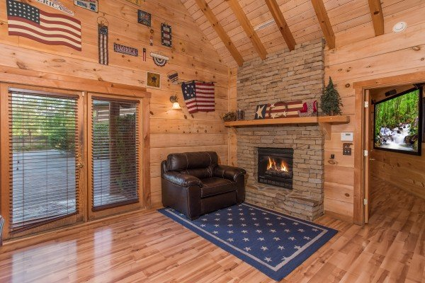 Fireplace and chair in the game room at Patriot Pointe, a 5 bedroom cabin rental located in Pigeon Forge