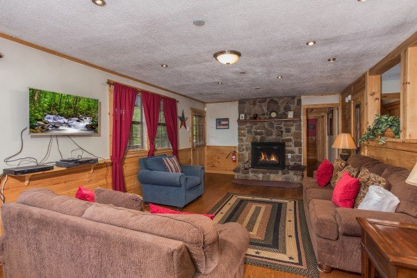 Living room with TV, fireplace, and seating at Patriot Pointe, a 5 bedroom cabin rental located in Pigeon Forge