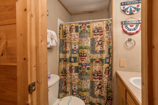 Bathroom with a tub and shower at Patriot Pointe, a 5 bedroom cabin rental located in Pigeon Forge