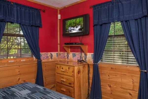 Bedroom with a dresser and TV at Patriot Pointe, a 5 bedroom cabin rental located in Pigeon Forge