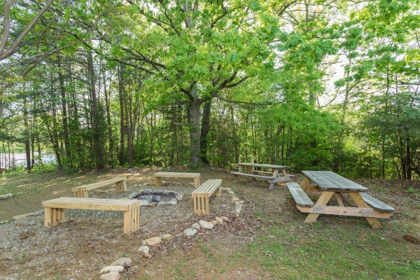 Fire pit with benches and picnic tables in the yard at Patriot Pointe, a 5 bedroom cabin rental located in Pigeon Forge