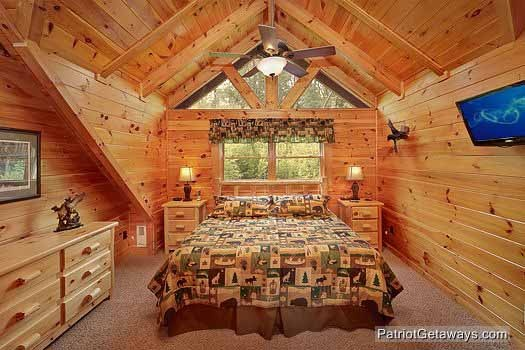 bedroom with king bed and tv at wilderness lodge a 3 bedroom cabin rental located in pigeon forge