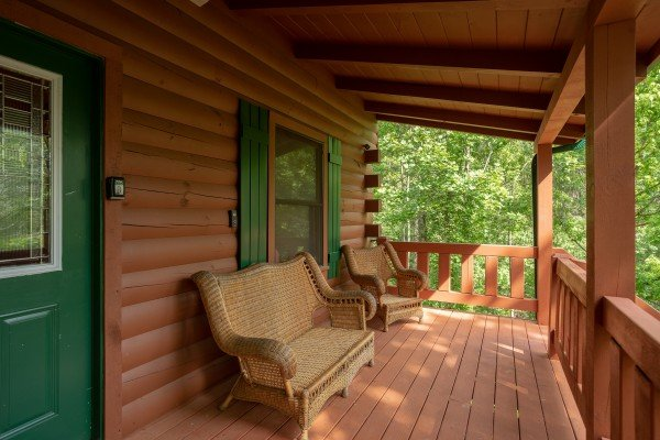 Wicker seating on the front porch at Mountain Breeze, a 1 bedroom cabin rental located in Pigeon Forge